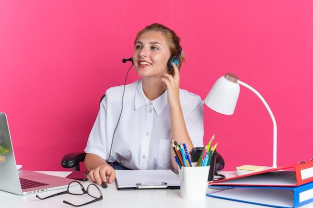 Sorridente ragazza bionda del call center che indossa la cuffia seduta alla scrivania con strumenti di lavoro toccando la cuffia guardando a lato