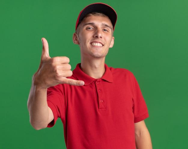 웃는 젊은 금발 배달 소년이 복사 공간이 있는 녹색 벽에 격리된 느슨한 제스처를 하고 있습니다.