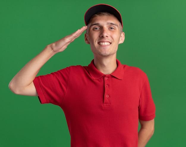 Улыбающийся молодой блондин посыльный делает жест салюта, изолированные на зеленой стене с копией пространства
