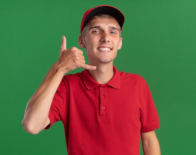 웃는 젊은 금발 배달 소년 제스처는 복사 공간이 있는 녹색 벽에 격리된 느슨한 기호를 걸고