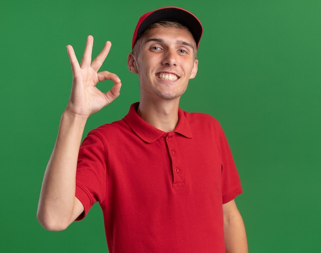Smiling young blonde delivery boy gestures ok hand sign isolated on green wall with copy space