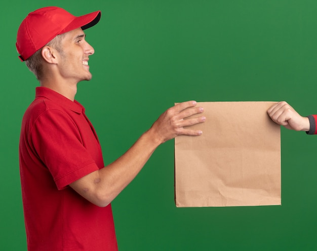 Smiling young blonde delivery boy gives paper package to someone isolated on green wall with copy space