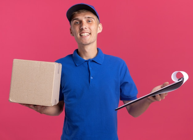 Sorridente giovane ragazzo delle consegne biondo che tiene scatola di cartone e appunti isolati sulla parete rosa con spazio di copia
