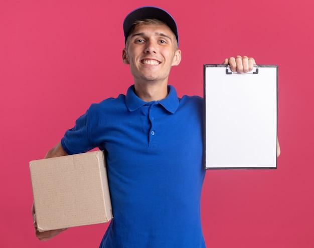 Sorridente giovane ragazzo delle consegne biondo che tiene appunti e scatola di cartone