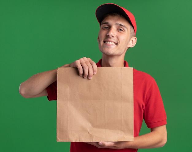 Sorridente giovane ragazzo delle consegne biondo che tiene il pacchetto di carta isolato sulla parete verde con spazio di copia