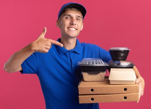 Улыбающийся молодой блондин курьер держит и указывает на пищевые контейнеры и пакеты на коробках для пиццы