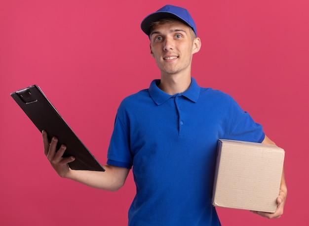 Il giovane ragazzo di consegna biondo sorridente tiene la scatola di cartone e la lavagna per appunti isolata sulla parete rosa con lo spazio della copia