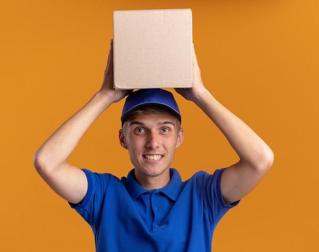 Улыбающийся молодой блондин курьер держит картонную коробку над головой