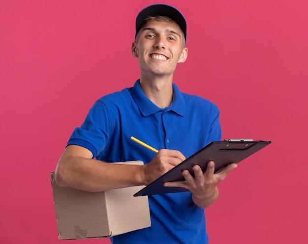 Il giovane ragazzo di consegna biondo sorridente tiene la scatola di cartone e scrive sulla lavagna per appunti con la matita isolata sulla parete rosa con lo spazio della copia
