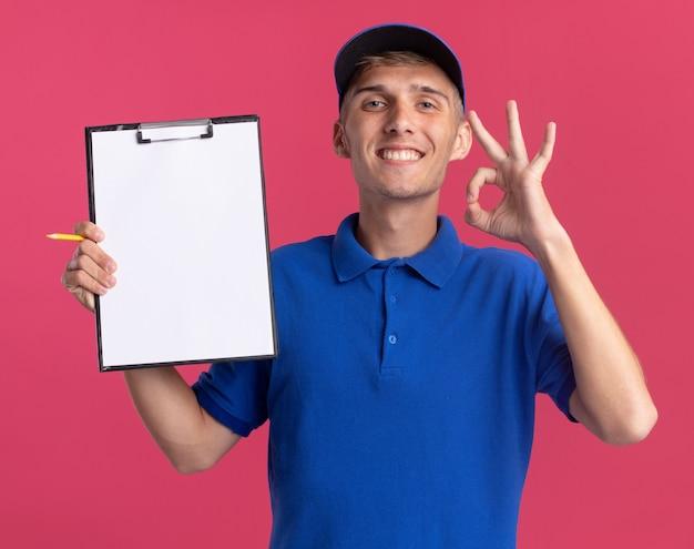 Il giovane ragazzo delle consegne biondo sorridente tiene la lavagna per appunti e fa un gesto ok con la mano