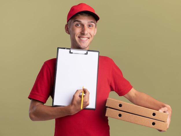 Il giovane ragazzo delle consegne biondo sorridente tiene gli appunti e le scatole della pizza pizza