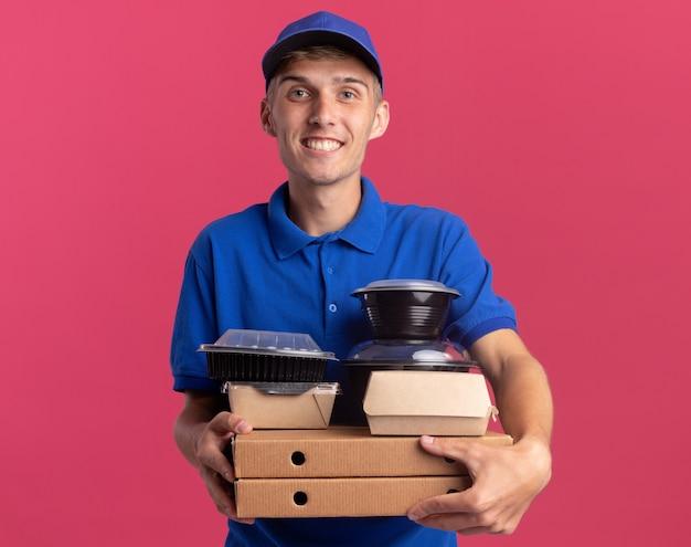 Улыбающийся молодой блондин курьер держит контейнеры для еды и пакеты на коробках для пиццы, изолированных на розовой стене с копией пространства