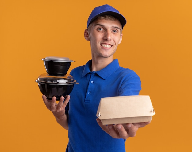 Smiling young blonde delivery boy holds food containers and package