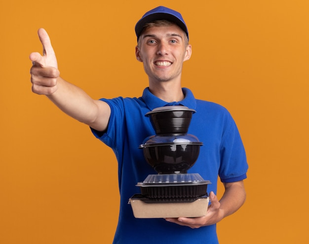 Smiling young blonde delivery boy holds food containers and points forward isolated on orange wall with copy space