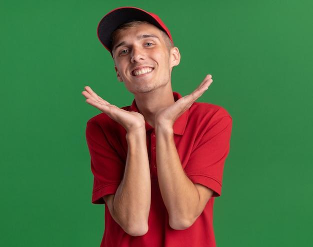 웃고 있는 젊은 금발 배달 소년은 복사 공간이 있는 녹색 벽에 격리된 손을 잡고 있습니다