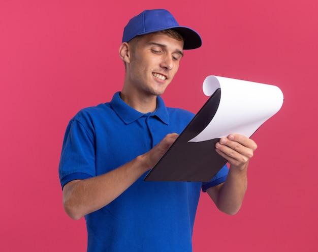 Il giovane ragazzo biondo sorridente delle consegne tiene ed esamina la lavagna per appunti sul rosa
