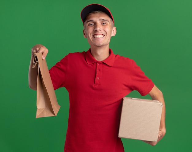 Smiling young blonde delivery boy holds paper package and cardbox isolated on green wall with copy space