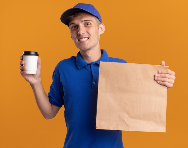 Il giovane ragazzo delle consegne biondo sorridente tiene il pacchetto e la tazza di carta