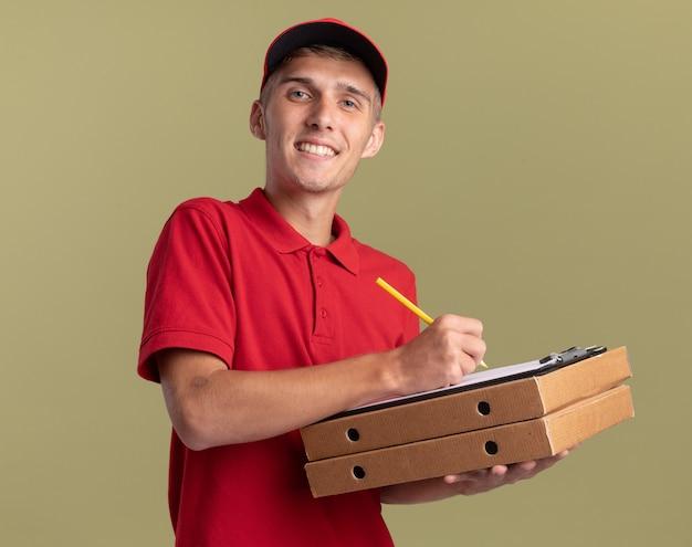 Il giovane ragazzo delle consegne biondo sorridente tiene matita e appunti su scatole per pizza