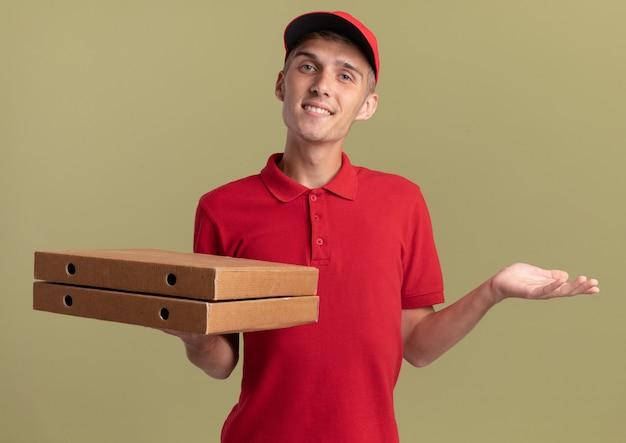 Il giovane ragazzo delle consegne biondo sorridente tiene le scatole della pizza e tiene la mano aperta