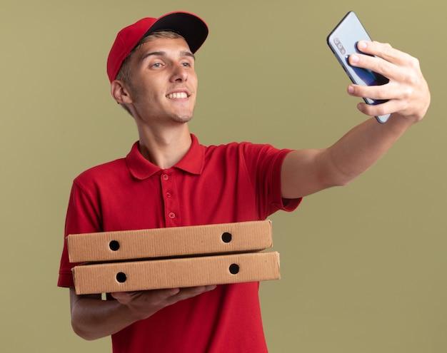Il giovane ragazzo delle consegne biondo sorridente tiene le scatole della pizza e guarda il telefono prendendo selfie