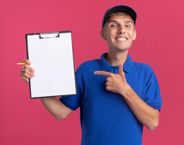 Il giovane ragazzo delle consegne biondo sorridente tiene e indica gli appunti