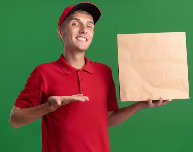 Il giovane ragazzo delle consegne biondo sorridente tiene e indica il pacchetto di carta