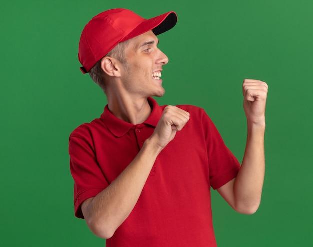 Il giovane ragazzo biondo sorridente delle consegne indica indietro ed esamina il lato sul verde