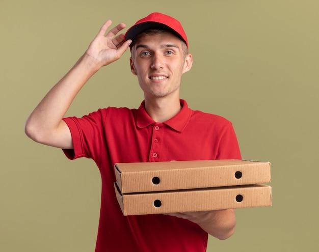 Il giovane ragazzo biondo sorridente delle consegne mette la mano sul cappuccio e tiene le scatole della pizza su verde oliva