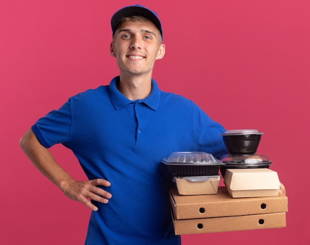 Smiling young blonde delivery boy puts hand on waist and holds food containers and packages on pizza boxes