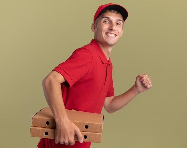 Улыбающийся молодой блондин посыльный стоит боком, держа коробки для пиццы, делая вид, что бежит изолированно на оливково-зеленой стене с копией пространства