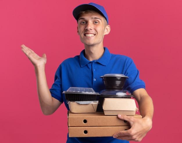 Il giovane ragazzo delle consegne biondo sorridente sta con la mano alzata e tiene contenitori per alimenti e pacchi su scatole per pizza