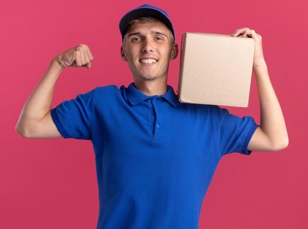 Улыбающийся молодой блондин курьер напрягает бицепсы и держит картонную коробку на плече