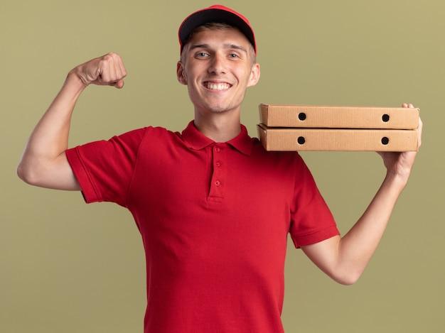 Il giovane ragazzo biondo sorridente delle consegne tende il bicipite e tiene le scatole della pizza sulla spalla su verde oliva
