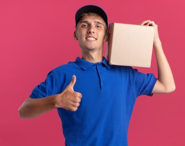 笑顔の若い金髪の配達の少年は親指を立てて、ピンクの肩にカードボックスを保持します