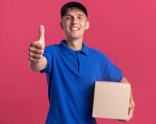 笑顔の若いブロンドの配達の少年は親指を立てて、カードボックスを保持します