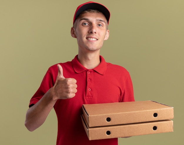 笑顔の若い金髪の配達の少年は親指を立てて、オリーブグリーンのピザの箱を保持します