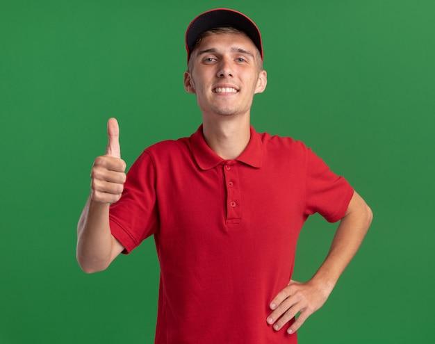 Il giovane ragazzo biondo sorridente delle consegne sfoglia sul verde