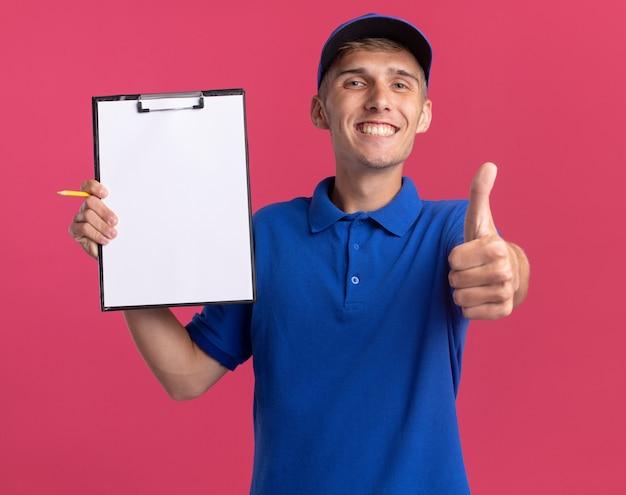 Il giovane ragazzo delle consegne biondo sorridente alza i pollici e tiene la lavagna per appunti isolata sulla parete rosa con lo spazio della copia