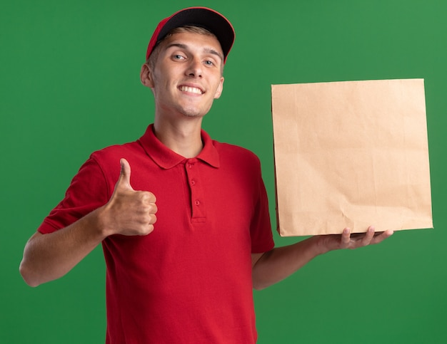 Il giovane ragazzo delle consegne biondo sorridente alza i pollici e tiene il pacchetto di carta isolato sulla parete verde con lo spazio della copia