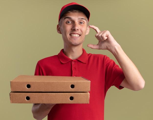 Il giovane ragazzo delle consegne biondo sorridente con scatole per pizza finge di tenere qualcosa di isolato sulla parete verde oliva con spazio per le copie