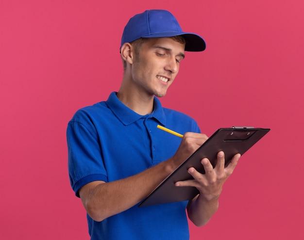 Il giovane ragazzo delle consegne biondo sorridente scrive sulla lavagna per appunti con la penna isolata sulla parete rosa con lo spazio della copia