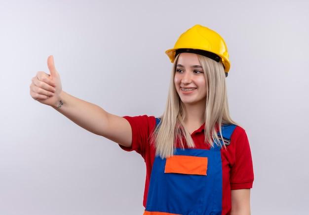 격리 된 공백에 왼쪽에 엄지 손가락을 보여주는 유니폼과 치과 교정기에 웃는 젊은 금발 엔지니어 작성기 소녀