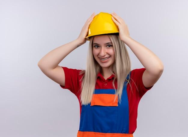 Улыбающаяся молодая блондинка инженер-строитель девушка в униформе в зубных скобах, надевая защитный шлем на изолированное белое пространство