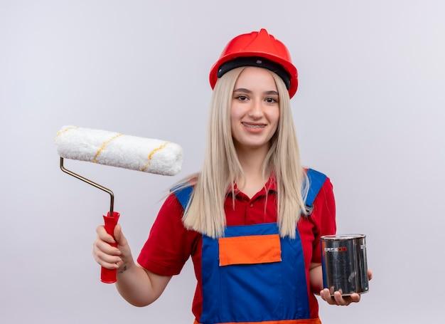 Sorridente giovane ragazza bionda ingegnere costruttore in uniforme in parentesi graffe dentali tenendo il rullo di vernice e vernice può su uno spazio bianco isolato
