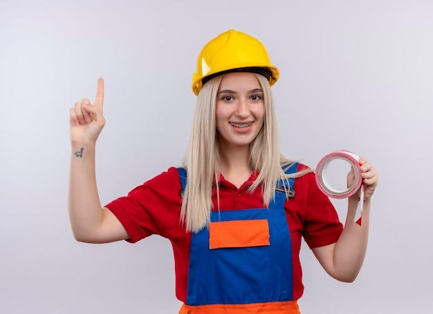 Sorridente giovane ragazza bionda ingegnere costruttore in uniforme in parentesi graffe dentali tenendo lo scotch e rivolto verso l'alto su uno spazio bianco isolato