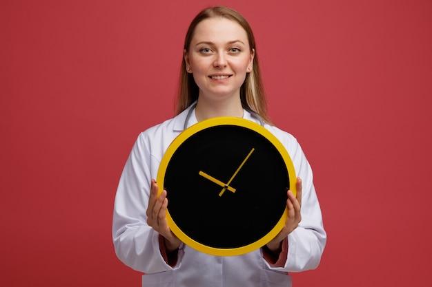 Giovane medico femminile biondo sorridente che porta veste medica e stetoscopio intorno all'orologio della holding del collo