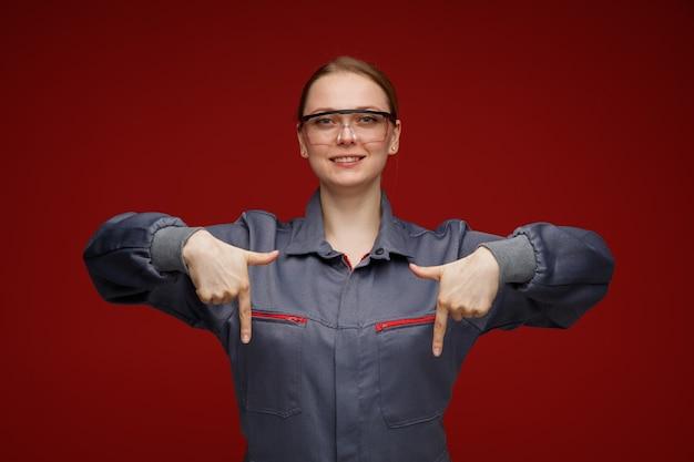 Sorridente giovane bionda ingegnere femminile che indossa uniformi e occhiali di sicurezza rivolti verso il basso