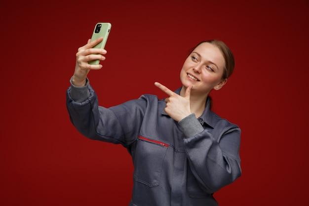 Sorridente giovane bionda ingegnere femminile che indossa uniformi tenendo selfie che punta al telefono cellulare