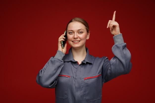 Sorridente giovane bionda ingegnere femminile indossa l'uniforme parlando al telefono rivolto verso l'alto
